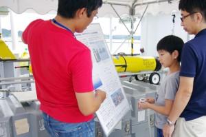 【写真5】水中グライダーの動作原理について説明を受ける親子連れ
