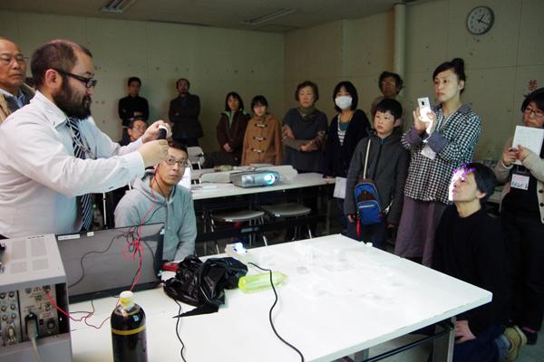 実物のシンチレータ、光検出器、電子回路を用いて、放射線測定装置がどうやって放射線を測定しているか、実演を交えながら鎌田准教授がわかりやすく解説した。