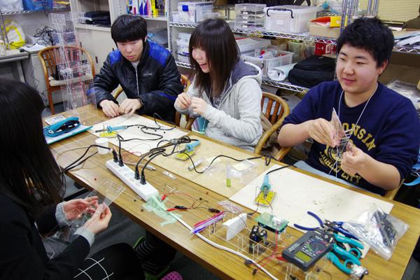 はんだ付けの練習後、LED点灯回路や光センサーの距離特性測定回路を作成する受講生たち。