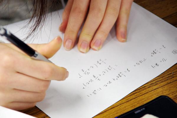 実験データの解析結果から重力加速度を算出し、その誤差について検証する受講生たち。