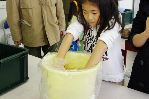 【写真5】麹菌や酵母の働きについて説明を受けた後、参加者たちは原料一つひとつの味を確かめながら、蒸かした大豆を潰し、米麹と塩と酵母を均一に混ぜて味噌を仕込んだ。