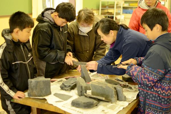 【写真7】雄勝玄昌石を専用の道具で割り、スレートへき開に沿って薄く剥がれるように割れる性質を体験する参加者のようす。