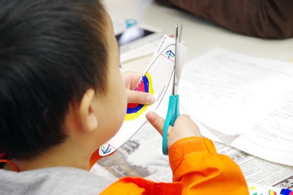 ケント紙に書かれた主翼・水平尾翼・垂直尾翼・補強紙に好きな絵を書いた後、子どもたちはやや緊張したようすで、線に沿って慎重に翼を切り取っていた