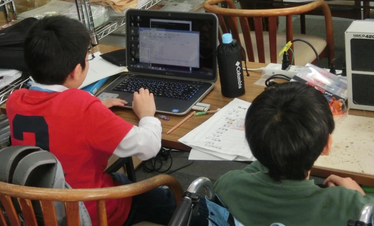 【写真5】電子工作をする小学生とプログラミングをする小学生