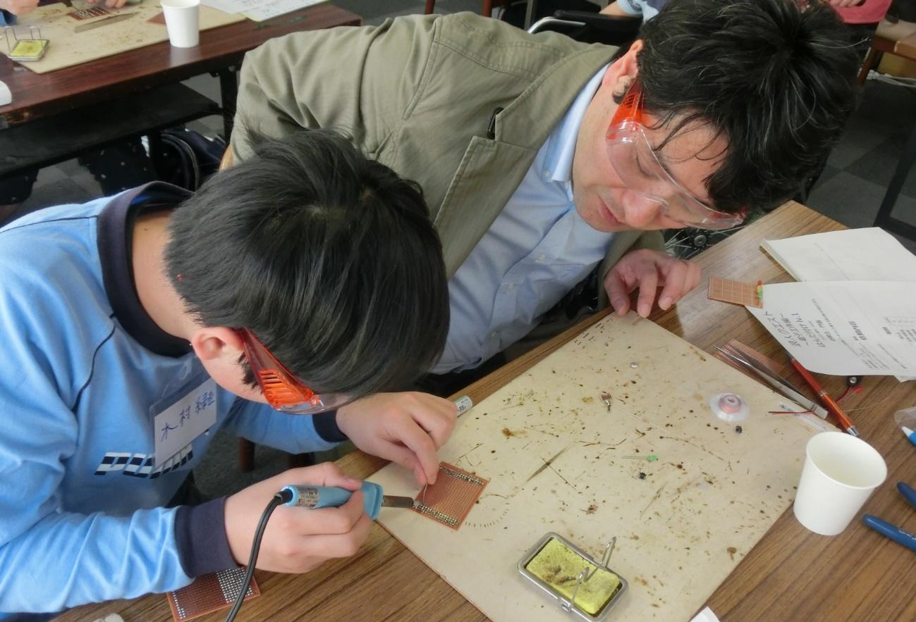 【写真8】中学生が大人に上手なはんだ付けの仕方を教えている様子